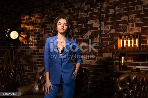 Close up. Loft. Portrait of a sexy girl in a business blue pantsuit. A black bra is seen in the neckline of her jacket. Spotlight and brown brick wall in the background. Copy space.