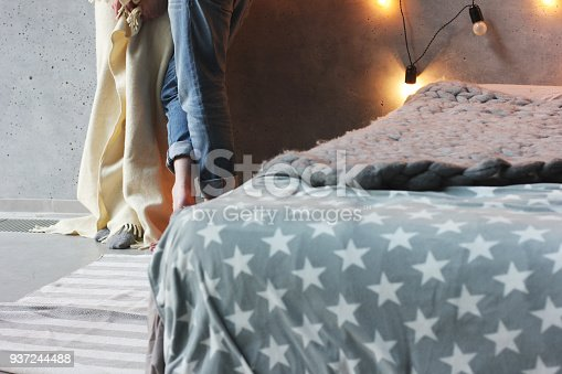 istock Loft style bedroom, bed with grey blanket and man and woman in the background 937244488