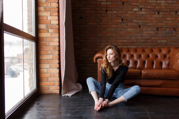 loft stil eingerichtet. sexuelle frau sitzt auf dem boden neben ledersofa in expressive pose, sieht am fenster. städtischen wohnung - hipster unterwäsche stock-fotos und bilder