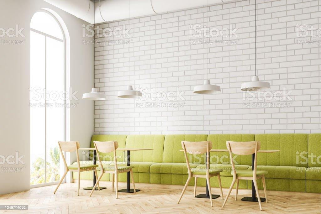 6915ee42df58 Sofá de esquina verde Loft ladrillo blanco restaurante foto de stock libre  de derechos