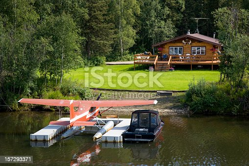 A log cabin with a floatplane and boat in the frontyard.