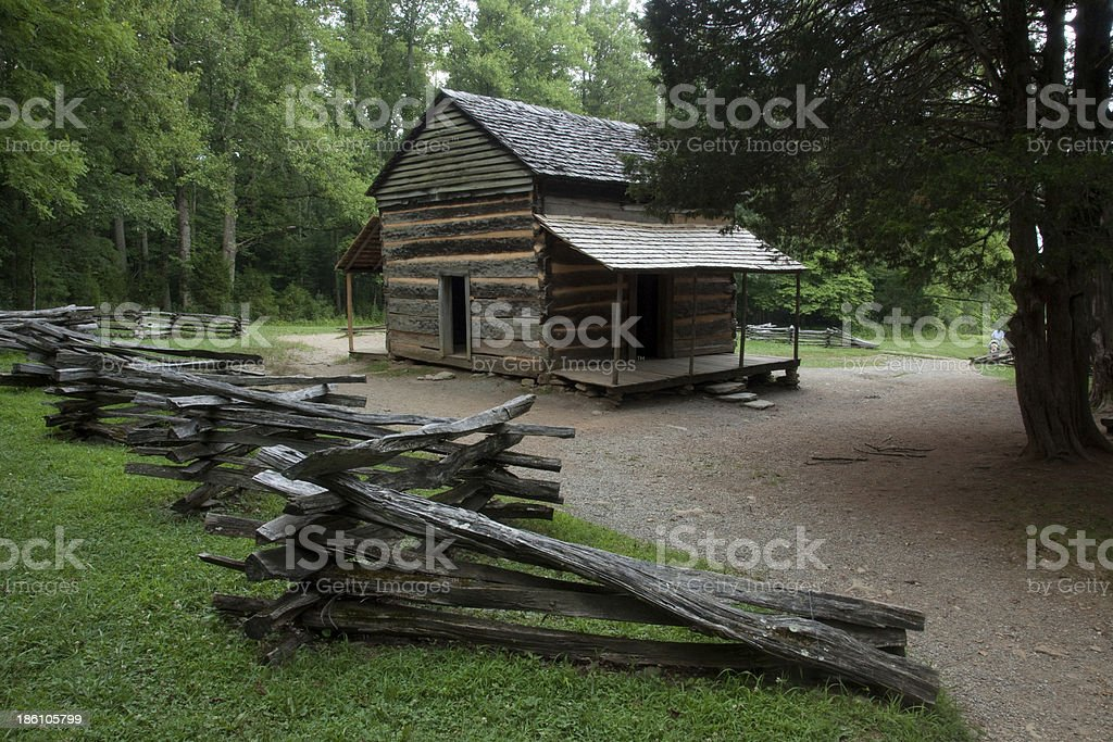 Log cabin and split rail fence in the woods stock photo