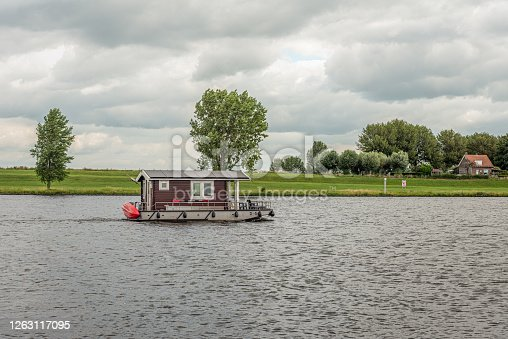 Electric powered log cabin boat with solar panels sailing on a Dutch river. It is a cloudy day in the summer season.