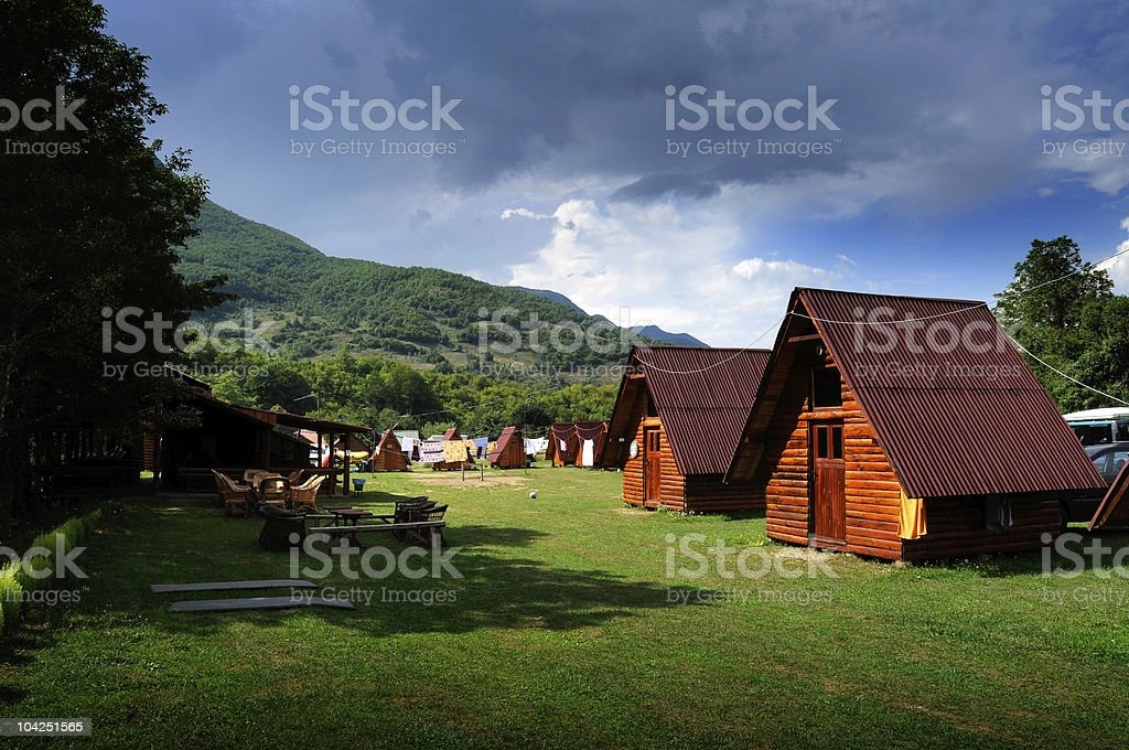 Log cabin camping site in the hills with picnic tables stock photo