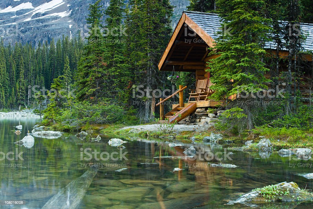Log cabin hidden in the trees by the Lake Ohara in Canada royalty-free stock photo