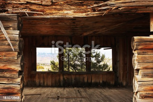 The view through an abandoned log cabin doorway and out through its windows to the desert landscape beyond.  Cottonwood, Arizona, 2013.
