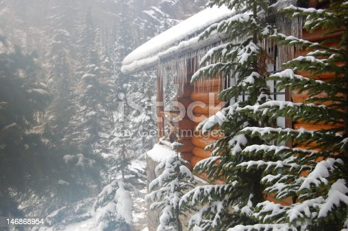 Log cabin amongst pine trees in the snow with icicles from the roof near Lake Louise