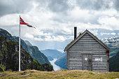 Kiellandbu and the Norwegian flag in front of Hardanger fjord in Norway.