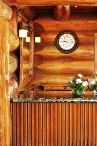 Upscale luxury log cabin style hotel rustic interior decor with granite countertop, mirror, lighting and clock at front desk.  Flagstaff, Arizona, 2012.