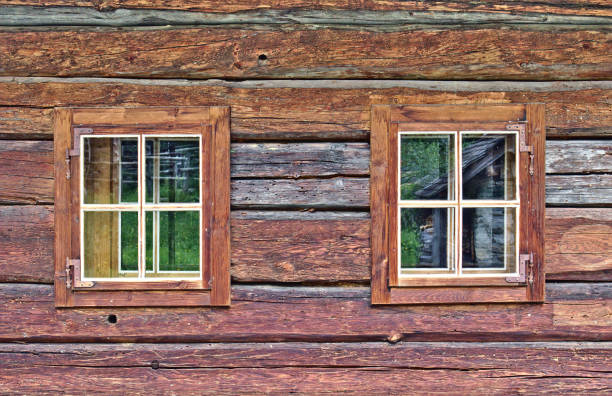Log cabin wall with two square windows stock photo