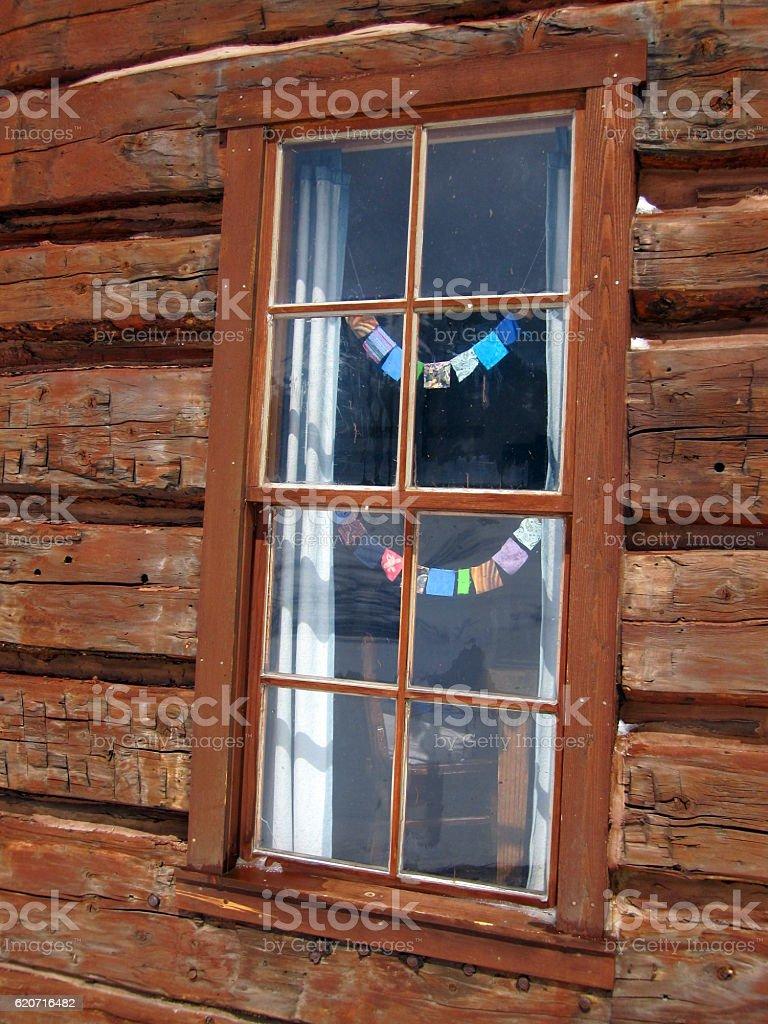 Log cabin window with tiny prayer flags stock photo