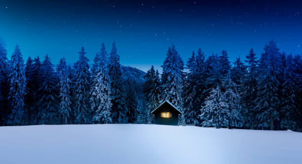 blockhütte mit glänzendem fenster im winterlichen wald - skihütte stock-fotos und bilder