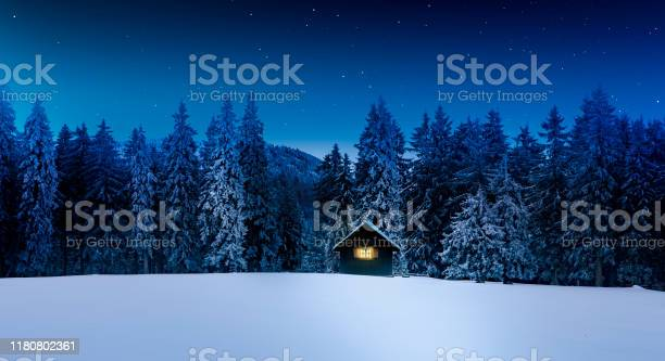 Photo of Log cabin with shining window in wintry forest