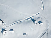 Log cabins and nordic skiing tracks in deep snow from above