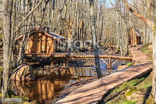 Varnhem, Sweden - April 14, 2018: Log cabins by a river with footbridges in a woodland at spring