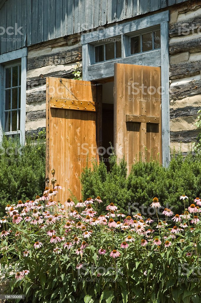 Log Church Front Door with Flowers in Sunlight royalty-free stock photo