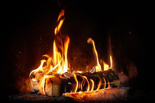 log fire and firewood in the fireplace for a cozy winter atmosphere