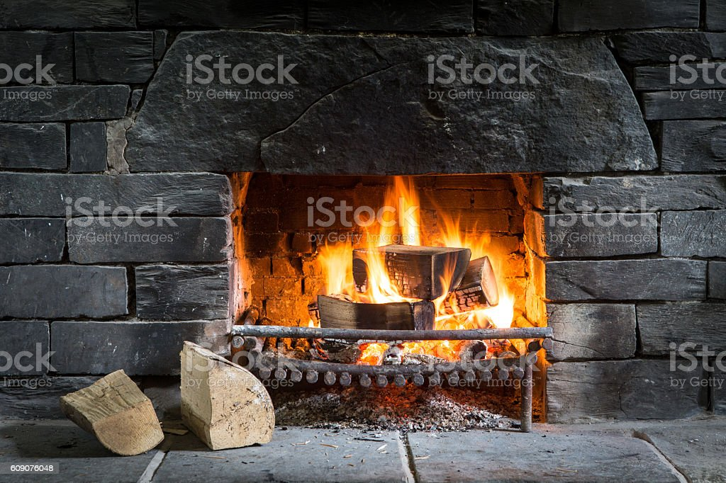 Log fire in open fireplace with black stone stock photo