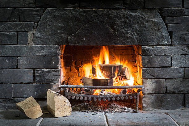 Log fire in open fireplace with black stone Log fire in open fireplace burner made from big black stones and two logs in foreground. log fire stock pictures, royalty-free photos & images