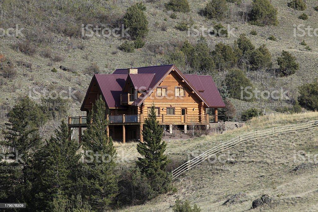 Log home on a rugged mountainside. stock photo