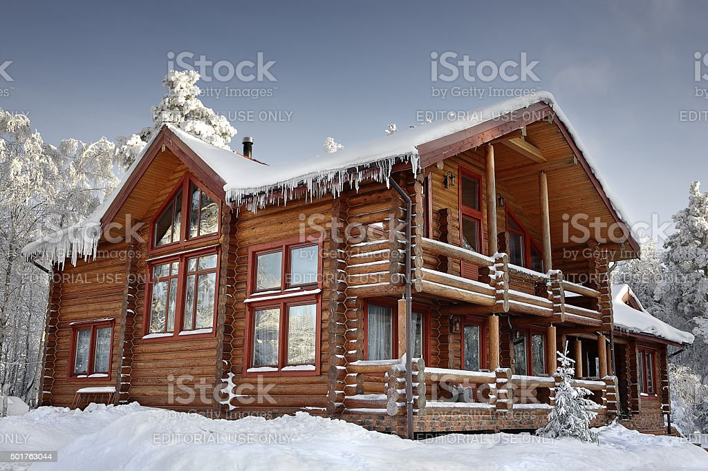 Log home winter with large windows, balcony and porch, daytime. stock photo