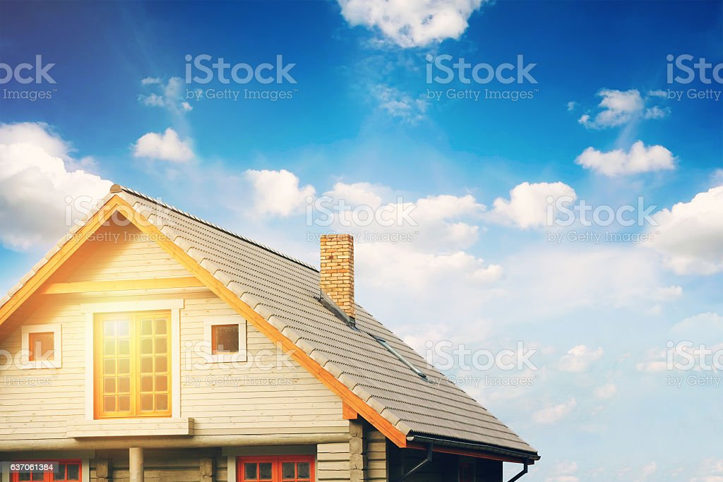 log lodge with gray tile roof against blue sky stock photo