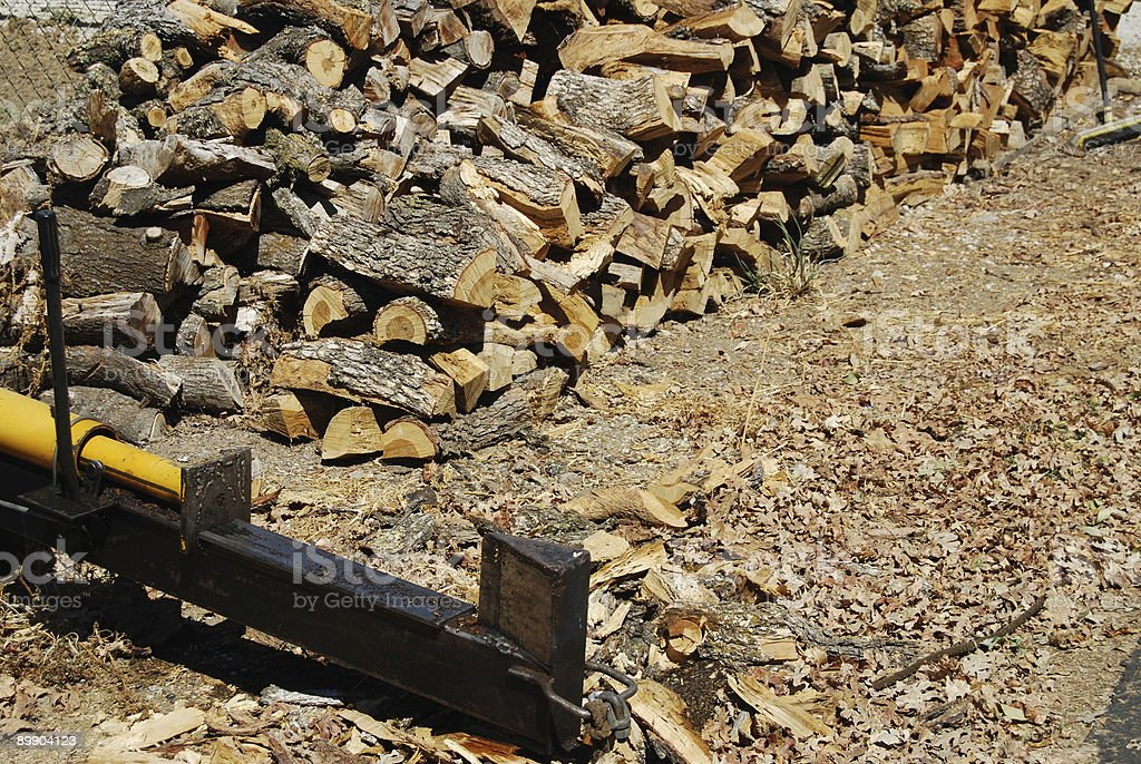 Log splitter and stacked firewood royalty-free stock photo