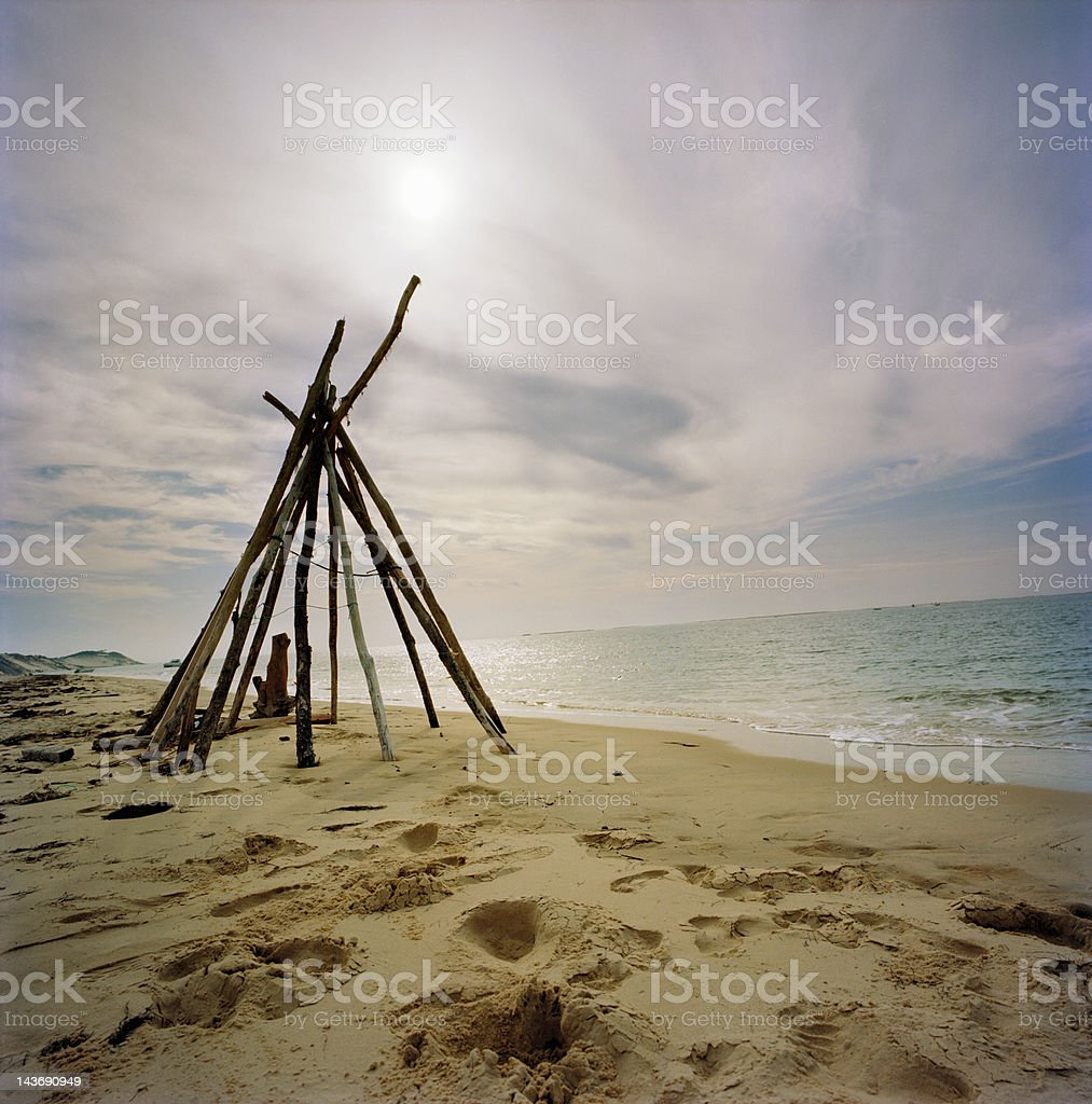 Log teepee on sandy beach stock photo
