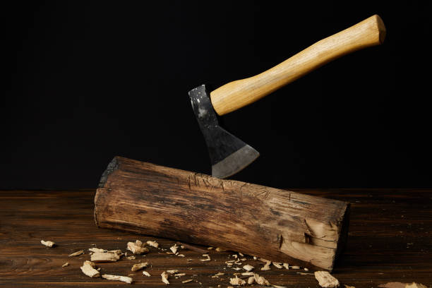 log with sticking axe and wooden pieces at table on black background stock photo