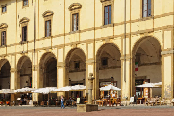 Loggia del Vasari - Arezzo Cafes and restaurants prepare for lunch under the yellow facade and elegant arches of Loggia del Vasari - Arezzo, Italy piazza grande stock pictures, royalty-free photos & images