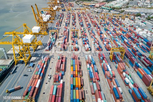 istock Logistics and transportation of container cargo freight ship with container crane in shipyard. Logistic import export business and transport industry. Aerial view taken from drone. 1073155866