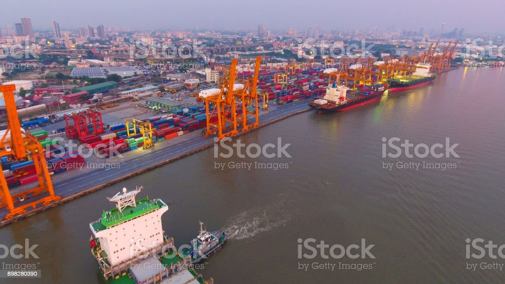 Logistics and transportation of Container Cargo ship and Cargo working crane bridge in shipyard stock photo