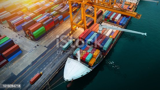 istock Logistics and transportation of Container Cargo ship and Cargo plane with working crane bridge in shipyard at sunrise, logistic import export and transport industry background 1019284718