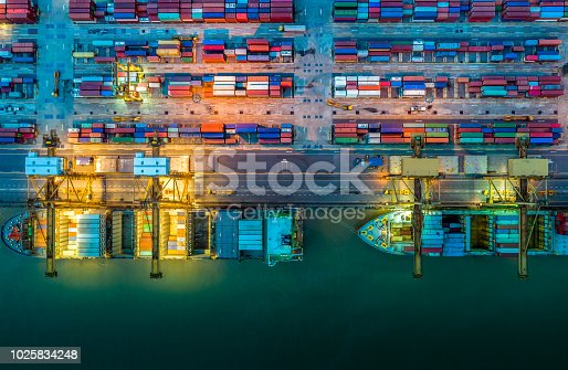 istock Logistics and transportation of Container Cargo ship and Cargo plane with working crane bridge in shipyard at night, logistic import export and transport industry background 1025834248