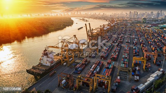 istock Logistics and transportation of Container Cargo ship and Cargo plane with working crane bridge in shipyard at sunset, logistic import export and transport industry background 1031235496