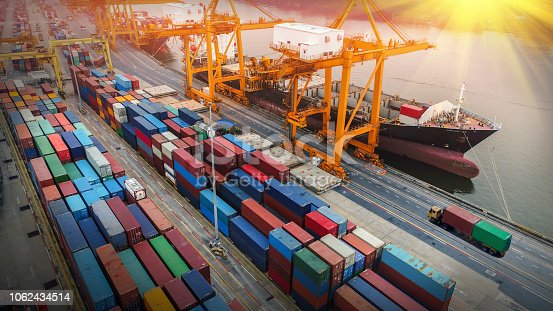 istock Logistics and transportation of Container Cargo ship and Cargo plane with working crane bridge in shipyard at sunrise, logistic import export and transport industry background 1062434514