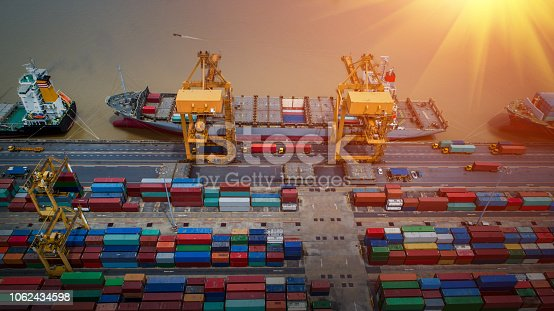istock Logistics and transportation of Container Cargo ship and Cargo plane with working crane bridge in shipyard at sunrise, logistic import export and transport industry background 1062434598