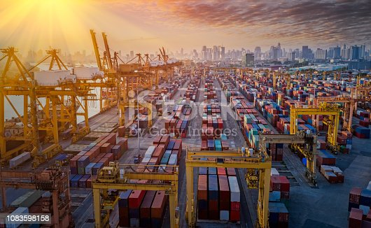 istock Logistics and transportation of Container Cargo ship and Cargo plane with working crane bridge in shipyard at sunrise, logistic import export and transport industry background 1083598158