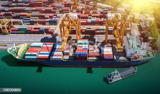 istock Logistics and transportation of Container Cargo ship and Cargo plane with working crane bridge in shipyard at sunrise, logistic import export and transport industry background 1092000654