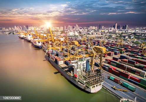 istock Logistics and transportation of Container Cargo ship and Cargo plane with working crane bridge in shipyard at sunrise, logistic import export and transport industry background 1092000682