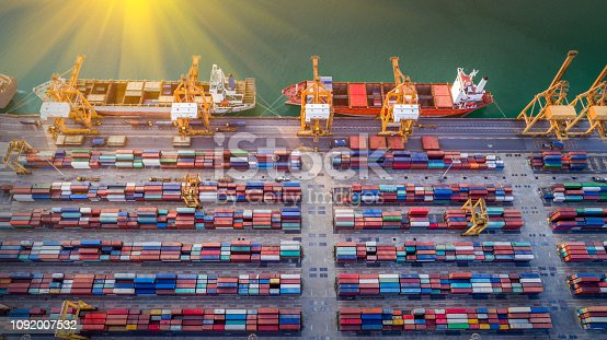 istock Logistics and transportation of Container Cargo ship and Cargo plane with working crane bridge in shipyard at sunrise, logistic import export and transport industry background 1092007532