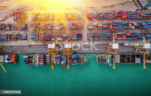 istock Logistics and transportation of Container Cargo ship and Cargo plane with working crane bridge in shipyard at sunrise, logistic import export and transport industry background 1092007546