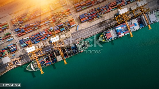 istock Logistics and transportation of Container Cargo ship and Cargo plane with working crane bridge in shipyard at sunrise, logistic import export and transport industry background 1125841834