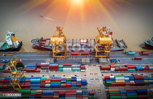 istock Logistics and transportation of Container Cargo ship and Cargo plane with working crane bridge in shipyard at sunrise, logistic import export and transport industry background 1126300694