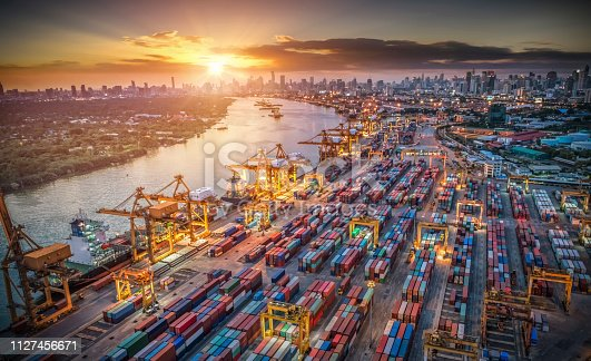 istock Logistics and transportation of Container Cargo ship and Cargo plane with working crane bridge in shipyard at sunset, logistic import export and transport industry background 1127456671