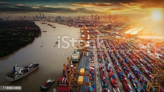 istock Logistics and transportation of Container Cargo ship and Cargo plane with working crane bridge in shipyard at sunrise, logistic import export and transport industry background 1130824350