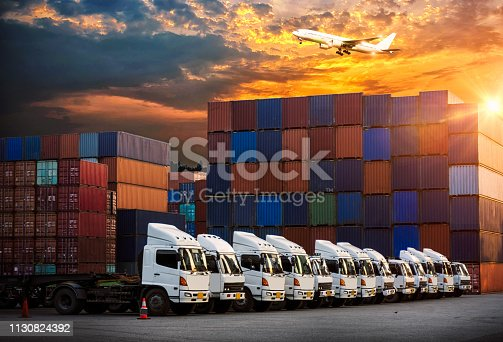 istock Logistics and transportation of Container Cargo ship and Cargo plane with working crane bridge in shipyard at sunrise, logistic import export and transport industry background 1130824392
