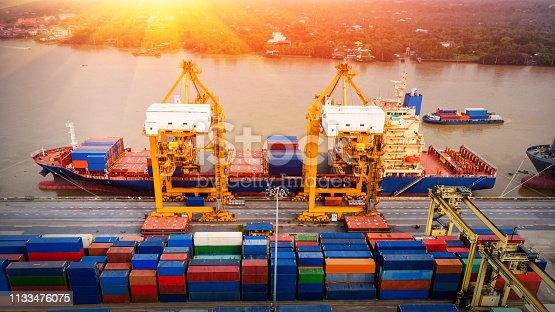istock Logistics and transportation of Container Cargo ship and Cargo plane with working crane bridge in shipyard at sunrise, logistic import export and transport industry background 1133476075