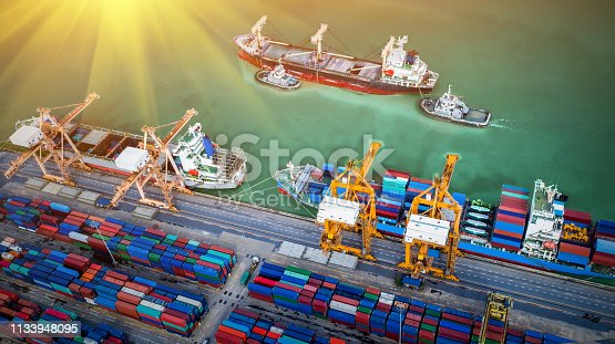 istock Logistics and transportation of Container Cargo ship and Cargo plane with working crane bridge in shipyard at sunrise, logistic import export and transport industry background 1133948095