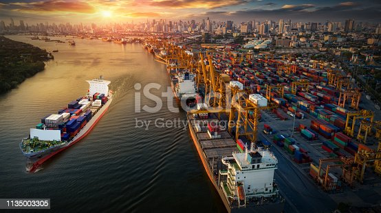 istock Logistics and transportation of Container Cargo ship and Cargo plane with working crane bridge in shipyard at sunrise, logistic import export and transport industry background 1135003305